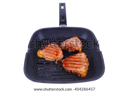 fresh grilled bloody beef steaks on black grill plate isolated on white background - stock photo