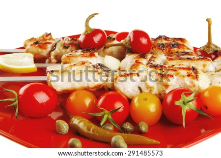 fresh grilled chicken shish kebab served with tomato cherry hot peppers on skewers over red plate isolated on white background - stock photo
