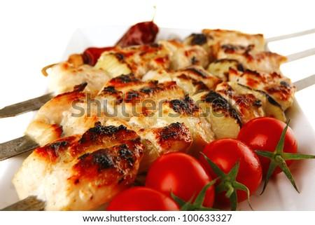 fresh grilled  pork shish kebab on white platter - stock photo