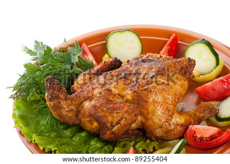 fresh grilled whole chicken with cucumber, raw tomatoes on plate with leaf lettuce isolated over white background - stock photo