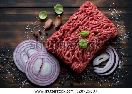 Fresh ground beef meat with seasonings, rustic wooden surface - stock photo