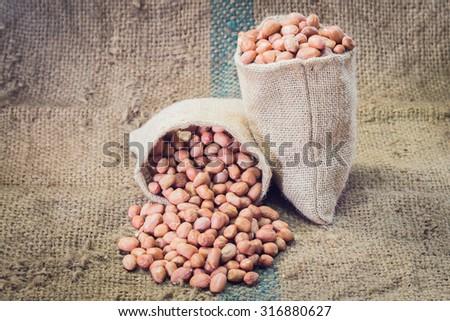 fresh ground nuts on sackcloth - stock photo