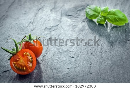 Fresh halved tomato and fresh basil arranged in the the opposite corners of the frame on a dark textured surface at a low angle perspective with copyspace - stock photo