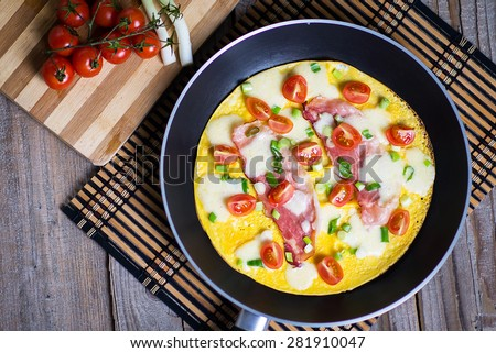 Fresh ham and cheese omelet in fry pan - stock photo