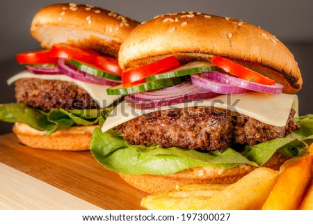 Fresh hamburger with vegetables and fries on wood plate - stock photo