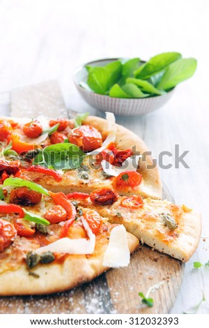 Fresh, handmade pizza with oven roasted tomatoes, peppers, capers, basil and shaved cheese on rustic wooden board  - stock photo