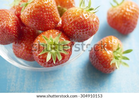 fresh healthy and tasty strawberries served in a glass bowl on a blue table. Some strawberries fallen out of the bowl.