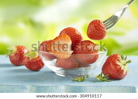 fresh healthy and tasty strawberries served in a glass bowl on a blue thable. one strawberry already attached to a fork ready to been eaten - stock photo