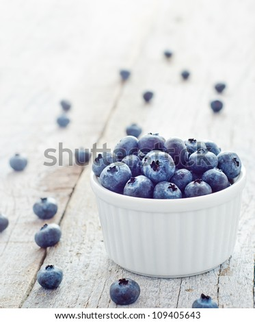 Fresh healthy blueberries in small bowl on wood table - stock photo