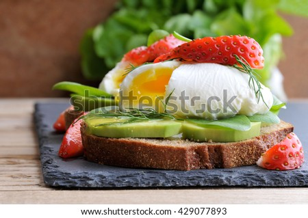 Fresh Healthy Breakfast:Poached egg on piece of rye bread with Avocado slices,Spinach and Strawberry .  - stock photo