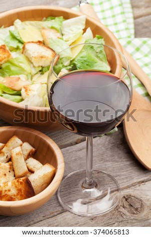 Fresh healthy caesar salad and red wine on wooden table - stock photo