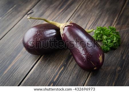 Fresh healthy eggplants on dark wooden background.  - stock photo
