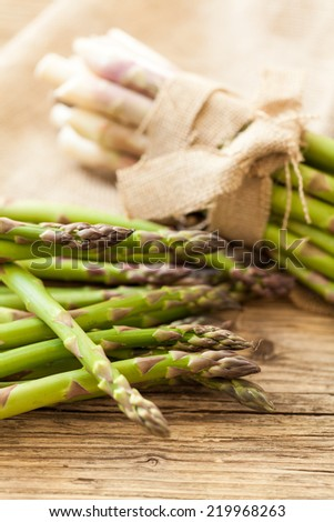 Fresh healthy green asparagus spears tied in bundles on a rustic wood surface on display at a farmers market for cooking a delicious appetizer or vegetable accompaniment to a meal - stock photo