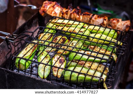 Fresh healthy green zucchini courgettes cucumber preparing on a barbecue grill over charcoal. Grilled zucchini slices. Vegetarian, Mediterranean cuisine. Delicious Food, vegetables on bbq party.  - stock photo