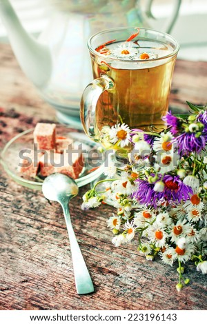 fresh healthy herbal tea in glass cup with flowers on wooden texture background - stock photo