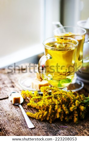 fresh healthy herbal tea in glass cups with flowers on wooden texture background - stock photo