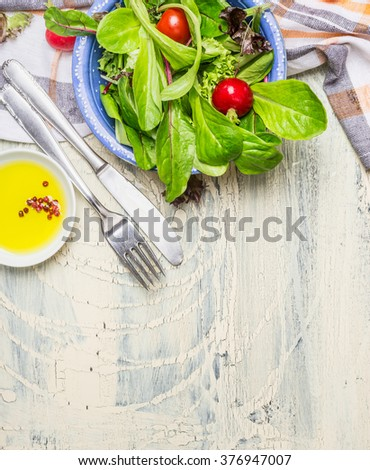 Fresh healthy salad with lettuce , cherry tomatoes and radish on light rustic background with cutlery and olive oil, top view, place for text. Healthy  lifestyle or detox diet food  concept - stock photo