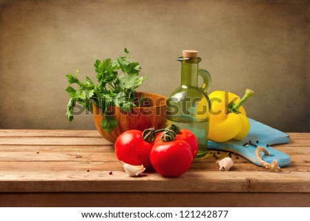 Fresh healthy vegetables on wooden table over grunge background - stock photo