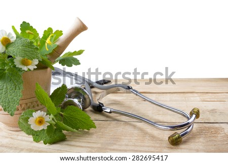 Fresh herb and stethoscope on wooden table. Alternative medicine concept. Isolated on whute background. - stock photo