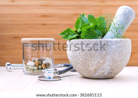 Fresh herbal leaves basil ,sage , mint ,holy basil ,fennel and capsule of herbal medicine alternative health care with stethoscope setup on wooden background. - stock photo