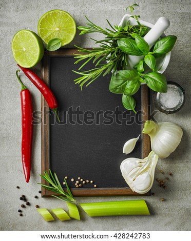 fresh herbs and spices and blackboard on gray kitchen table, top view - stock photo