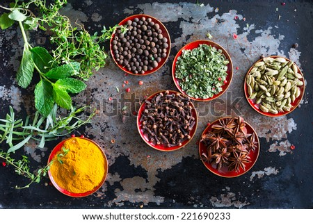 Fresh herbs and whole spices displayed on a vintage metal cooking sheet. Overhead top view shot looking down. - stock photo