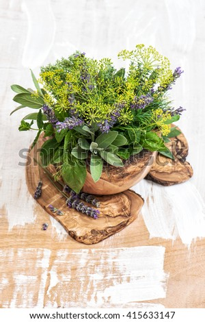Fresh herbs dill, thyme, sage, lavender, mint, basil. Olive wood kitchen utensils. Healthy food ingredients - stock photo