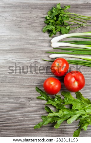 Fresh herbs: green onion, arugula, tomatoes and dill on a wooden table - stock photo