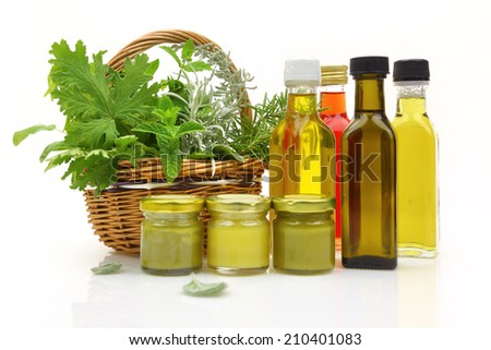 Fresh herbs in wicker basket and natural cosmetics  - stock photo
