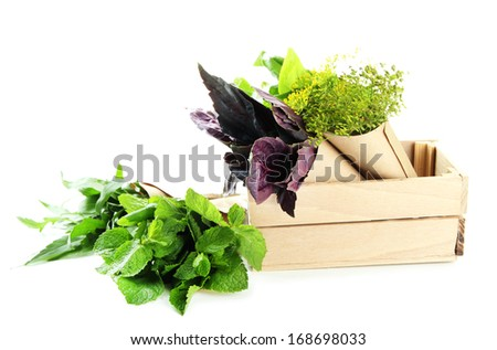 Fresh herbs in wooden crate, isolated on white - stock photo