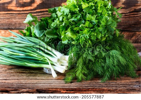 Fresh herbs on  wooden board.  Dill,  green onion, parsley - stock photo