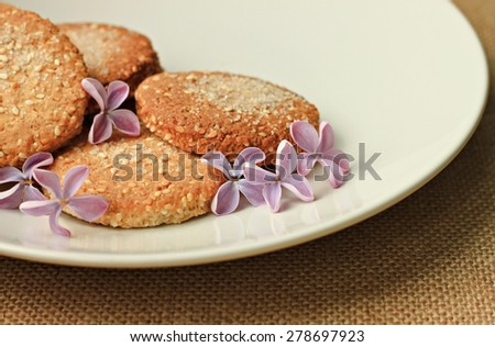 fresh home baked oatmeal cookies on plate with flowers for breakfast - stock photo