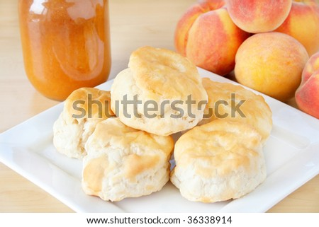 Fresh home made biscuits stacked on a white plate with home made peach preserves in the background along with fresh peaches. - stock photo