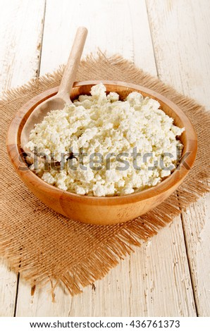 fresh home made cottage cheese with wooden spoon in a wooden bowl - stock photo
