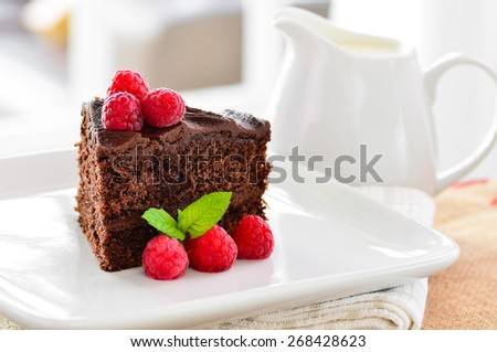 Fresh home made sticky chocolate cake with raspberries and a jug of fresh pouring cream in the background - stock photo