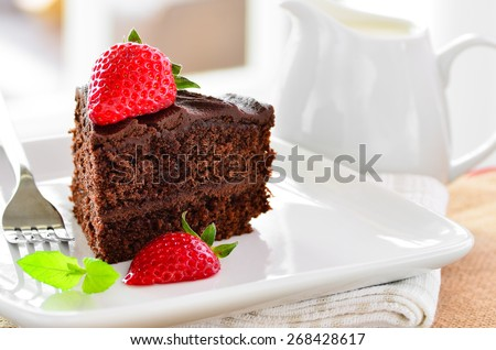 Fresh home made sticky chocolate cake with strawberries and raspberries, with a jug of fresh pouring cream - stock photo