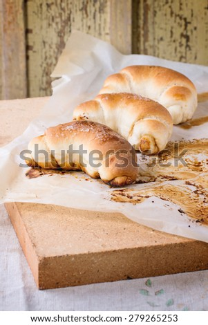 Fresh homemade baked crescent rolls on baking paper and oven stone over light gray tablecloth - stock photo