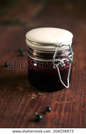 Fresh homemade blackcurrant jam, confiture or marmalade in a glass jar with blackcurrant berries on the wooden table, rustic style, selective focus - stock photo