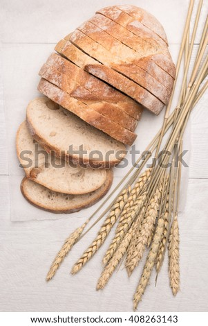 Fresh homemade bread and wheat spike on wooden background. Top view with copy space. - stock photo