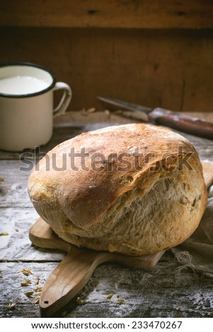 Fresh homemade bread on wooden cutting board with vintage knife and mug of milk served over wooden table with flour - stock photo