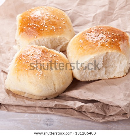 Fresh homemade bread rolls with sesam seeds on table - stock photo