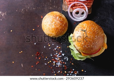 Fresh homemade burger on black slate and raw cutlet and sliced onion, served with sea salt and pepper over dark background. Top view. With copy-space on left. - stock photo
