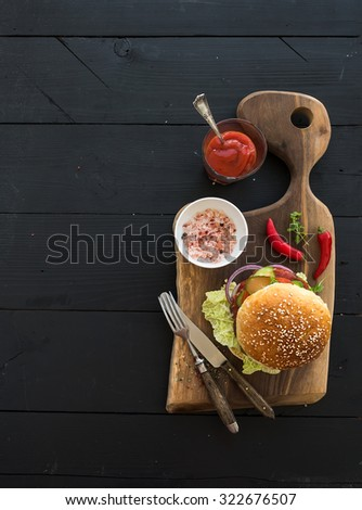 Fresh homemade burger on dark serving board with spicy tomato sauce, sea salt over dark wooden background. Top view, copy space - stock photo