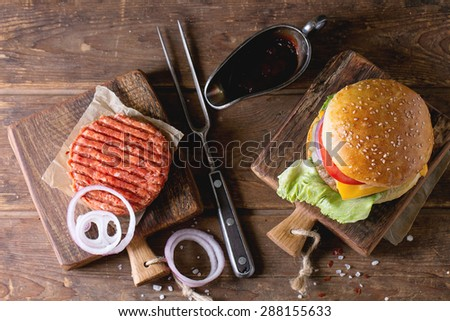 Fresh homemade burger on little cutting board and raw cutlet and sliced onion, served with ketchup sauce and meat fork over wooden table. Dark rustic style. Top view - stock photo