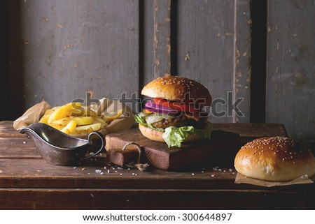 Fresh homemade burger on little cutting board with grilled potatoes, served with ketchup sauce and sea salt over wooden table with gray wooden background. Dark rustic style. - stock photo