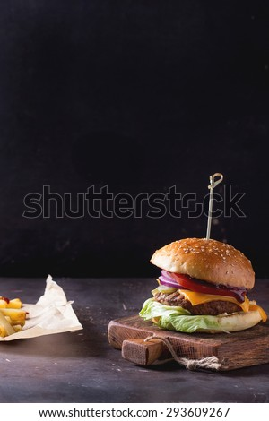 Fresh homemade burger on little wooden cutting board and grilled potatoes over dark background. Withcopy space on top - stock photo
