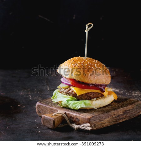 Fresh homemade burger on little wooden cutting board over dark background. Square image with selective focus - stock photo