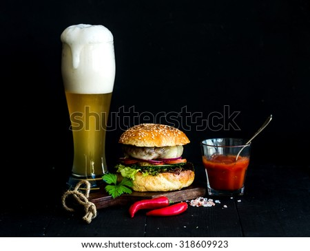 Fresh homemade burger on wooden serving board with spicy tomato sauce, sea salt, herbs and glass of light beer over black  background - stock photo
