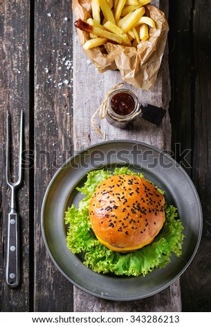 Fresh homemade burger with black sesame seeds and fried potatoes in backing paper, served with ketchup sauce in glass jar and meat fork on wooden board over old wooden surface. Rustic style. Top view - stock photo