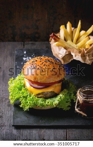 Fresh homemade burger with black sesame seeds on black slate board with fried potatoes, served with ketchup sauce in glass jar and sea salt over wooden table with dark background. Dark rustic style. - stock photo